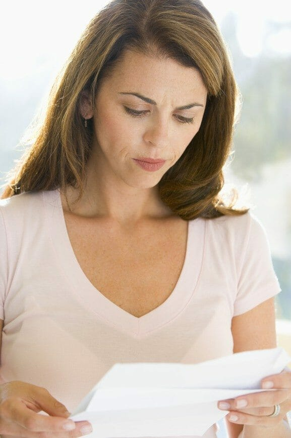 Woman reading letter and frowning