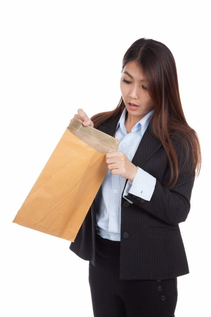 Young Asian businesswoman surprise look inside brown envelopes