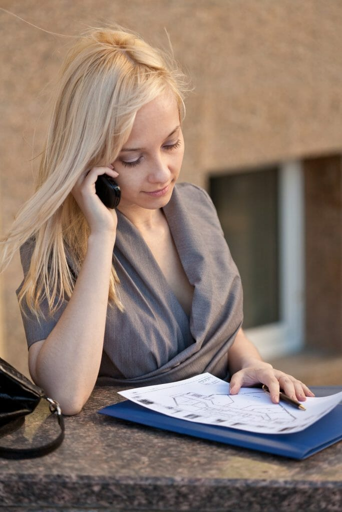 Beautiful woman sitting, calling to phone and reading documents