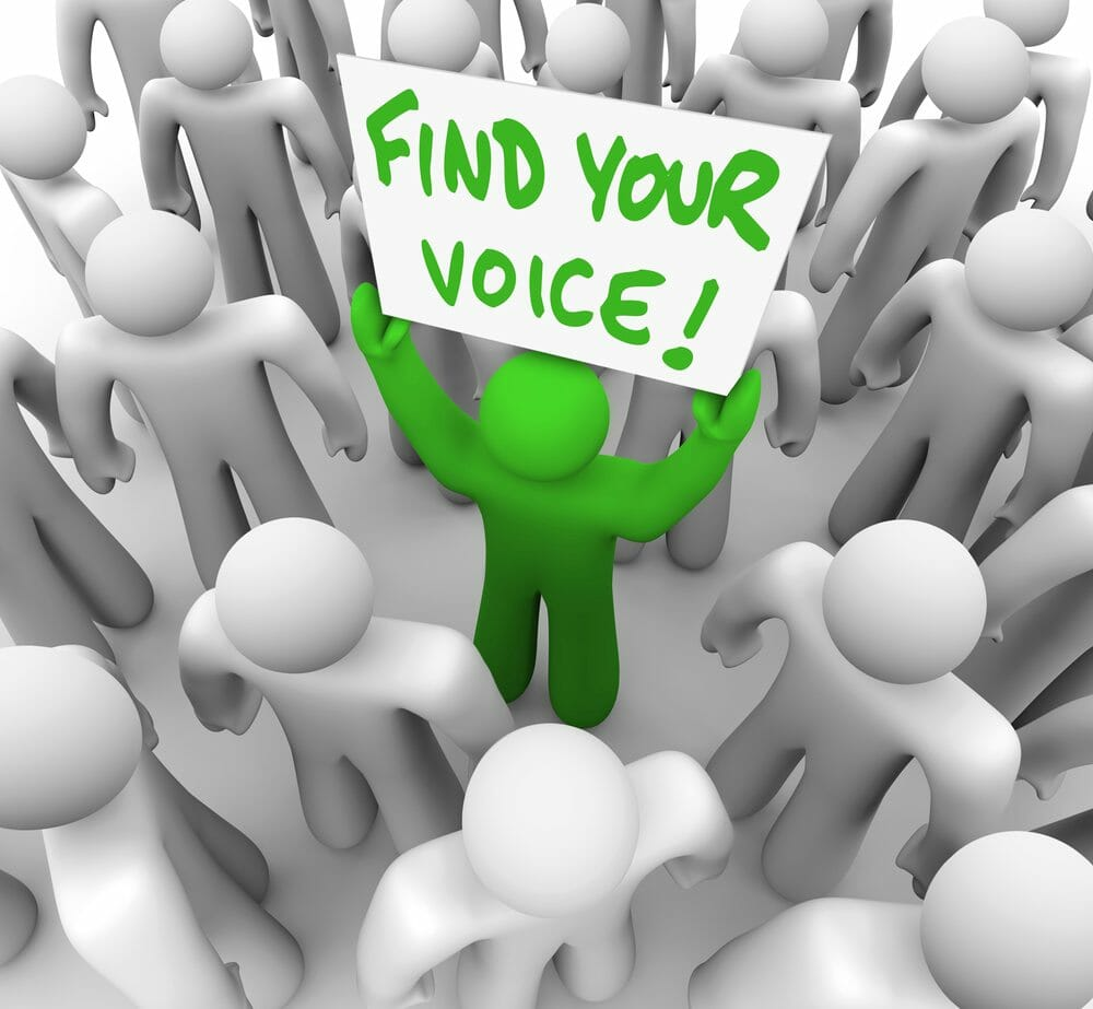 Find Your Voice Man Holding Sign in Crowd – Confidence